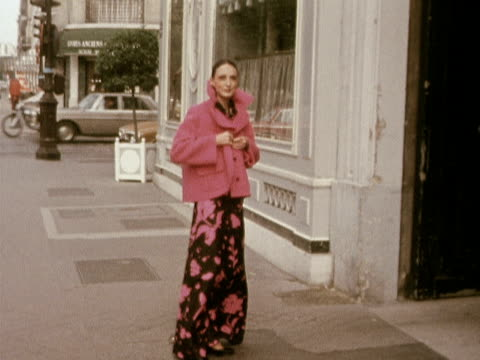 A model wears a silk evening dress with a pink jacket designed by Marc Bohan for Dior 1972