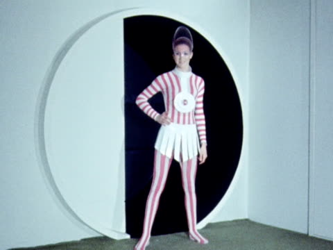 A model wears a stripped catsuit with a plastic frilled skirt and large plastic necklace 1970