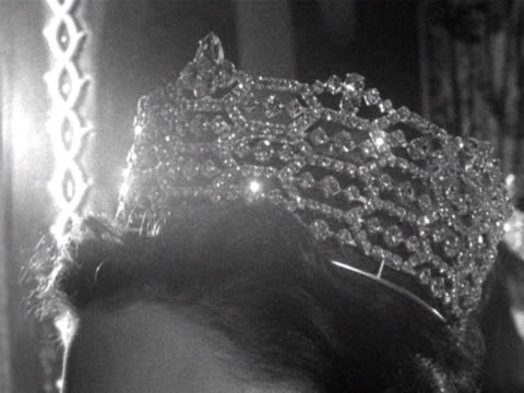 A model wears a tiara and necklace at a fashion show 1960