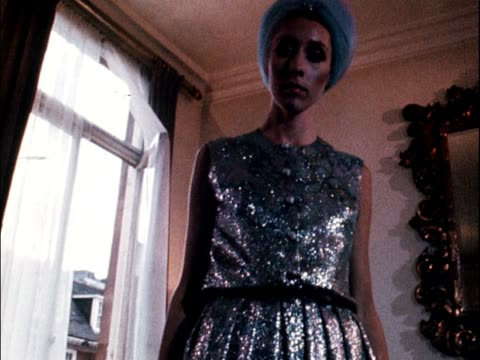 a model wears a turban and a silver blue evening outfit with full trousers designed by mattli 1968 - 頭飾り点の映像素材/bロール