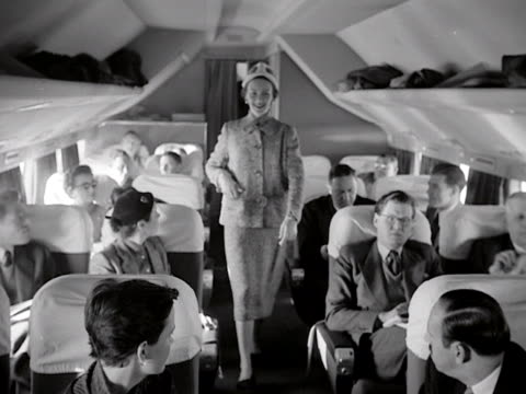 a model wears a tweed skirt and jacket during an inflight fashion show onboard a passenger aircraft - flugpassagier stock-videos und b-roll-filmmaterial