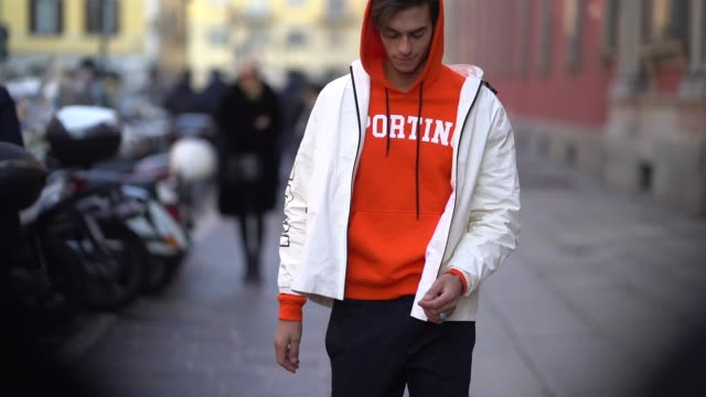 A model wears a white jacket an orange hoodie during Milan Menswear Fashion week Fall/Winter 2018/19 on January 14 2018 in Milan Italy