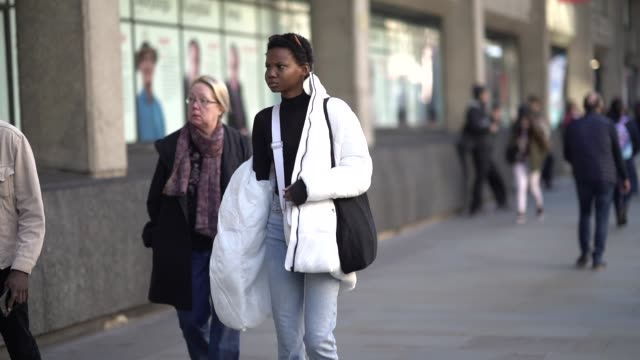 stockvideo's en b-roll-footage met a model wears a white puffer jacket cropped jeans socks sneakers shoes a black mesh top during london fashion week february 2019 on february 15 2019... - ski jack