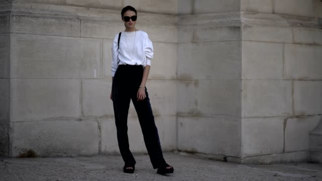 A model wears a white top black velvet pants sandals outside the Ralph Russo show during Paris Fashion Week Haute Couture Fall/Winter 20172018 on...