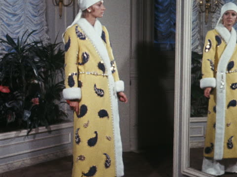A model wears a yellow and white embroidered coat worn over evening pyjames designed by Marc Bohan for House of Dior