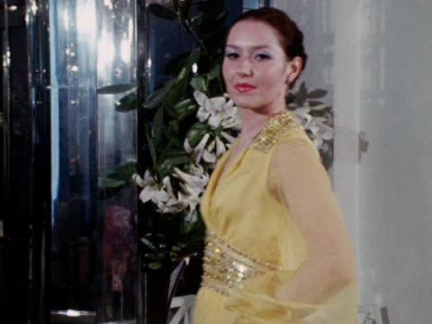 vídeos y material grabado en eventos de stock de a model wears an embroidered yellow dress with diaphanous sleeves designed by norman hartnell - translúcido