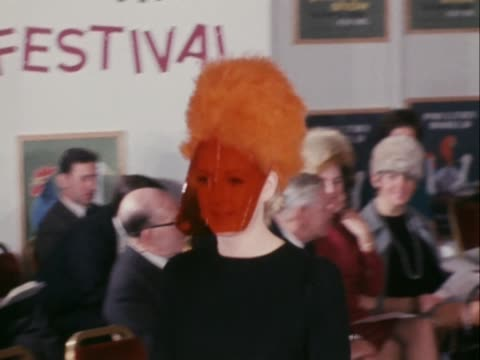 stockvideo's en b-roll-footage met a model wears an orange feather hat with a red visor at the feather hat festival in london - dameskleding