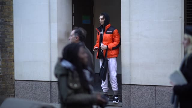A model wears an orange puffer coat a black hoodie sweater during London Fashion Week Men's January 2018 on January 07 2018 in London England