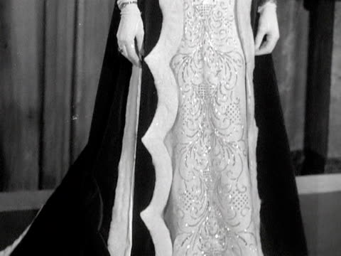 vidéos et rushes de a model wears diamond earrings necklace and tiara while wearing the robes of a peeress at a jewellery fashion show 1952 - pierre précieuse