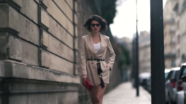 a model wears large earrings sunglasses a white top a beige wrapover jacket a black cord belt with pompons a red ysl clutch outside elie saab during... - modewoche stock-videos und b-roll-filmmaterial