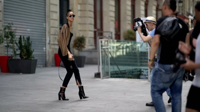 vídeos y material grabado en eventos de stock de a model wears sunglasses a bomber jacket a black top black ripped jeans a studded bag black boots outside the jean paul gaultier show during paris... - rasgado