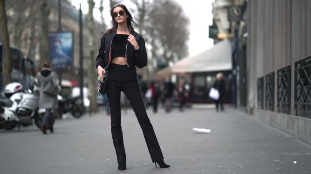 A model wears sunglasses a bomber jacket black pants a bare belly top outside Elie Saab during Paris Fashion Week Haute Couture Spring/Summer 2018 on...