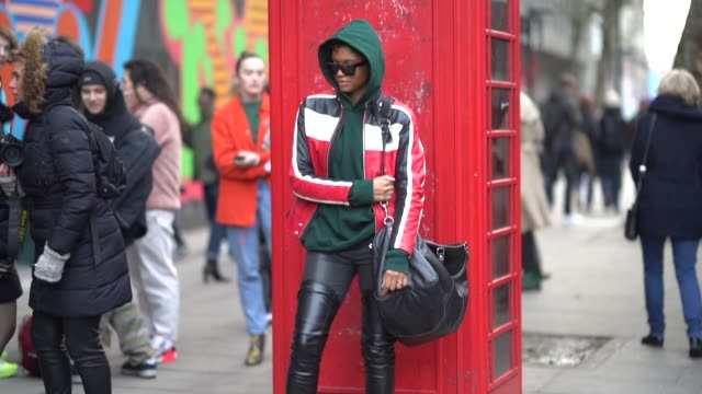 a model wears sunglasses a green hoodie sweater a blue white and red striped leather jacket black leather pants black thigh high leather boots with... - hose stock-videos und b-roll-filmmaterial