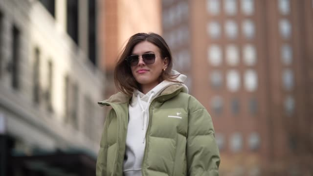 model wears sunglasses, a white hoodie sweater, a green puffer jacket, a bag, black leggings, white sneakers, during new york fashion week fall... - leggings stock videos & royalty-free footage