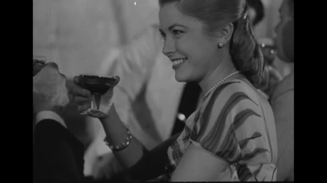 stockvideo's en b-roll-footage met modeling session - close up pan starting at hem of grace kelly evening dress to her full figure sipping cocktail, clicks glasses with unidentified... - zoom out
