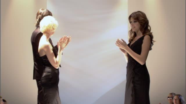 cu zo ws models applauding designer on catwalk, then walk backstage / london, england, uk - この撮影のクリップをもっと見る 1064点の映像素材/bロール