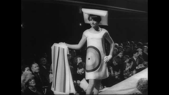 models come through glass partition to pose in clothing by french designer jacques esterel / models show boxy designs with linear shape / model in... - 1966年点の映像素材/bロール