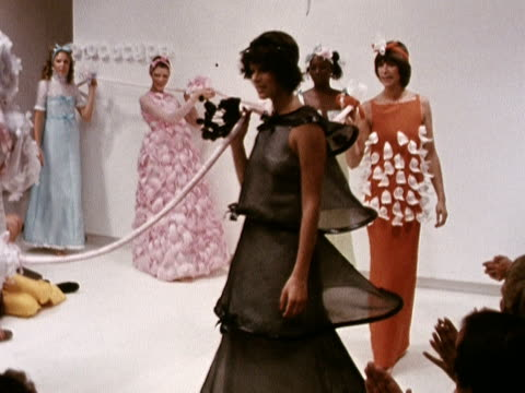 vídeos de stock, filmes e b-roll de models dance in a circle whilst holding a rope and wearing a variety of unconventional evening gowns at a courreges fashion show in paris 1972 - model t