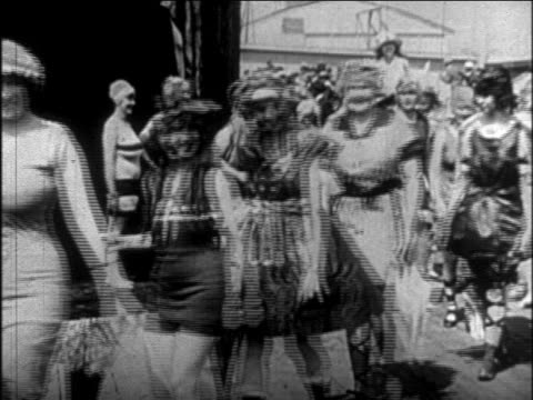 models in antique bathing suits walking past camera in outdoor fashion show / newsreel - 1926年点の映像素材/bロール