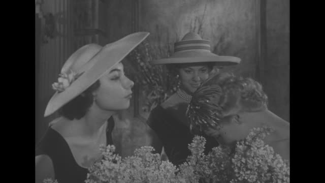 Models in midst of crowded floral arrangements / models smelling flowers MarieChristiane hat at left decorated with white lilies / VS woman with...