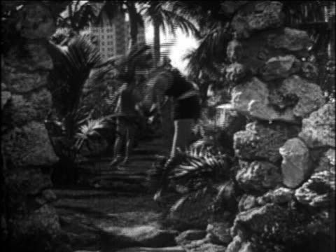b/w 1926 models in swimsuits frolicking + doing acrobatics amongst palm trees / newsreel - 1926 stock videos & royalty-free footage