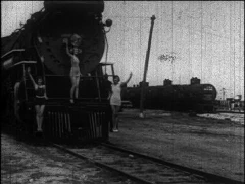 b/w 1926 models in swimsuits standing on steam train coming towards camera + waving / newsreel - 1926 bildbanksvideor och videomaterial från bakom kulisserna
