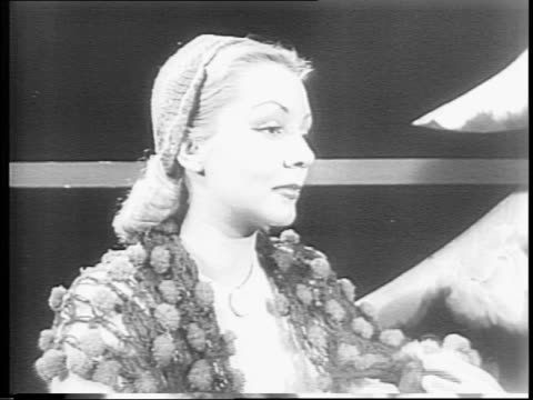 models, including mary armstrong, maria morton and vicki roberts, on stage in costumes for 'out of doors' / model in white wool coat and turban,... - 1943 stock-videos und b-roll-filmmaterial