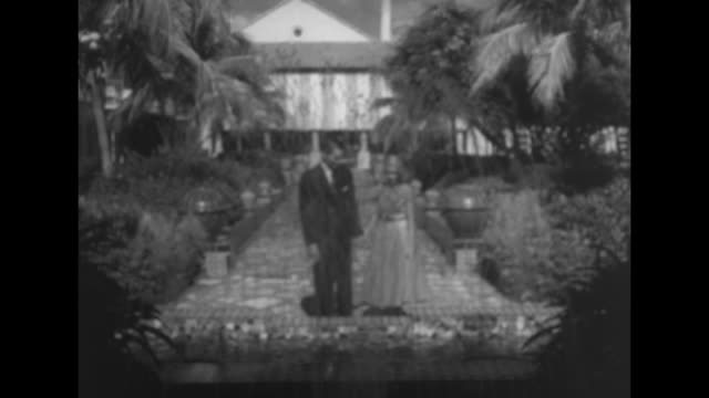 LS models Mark and Joan walk garden path to small pool / they sit by garden pool waiter brings in cocktails on a tray / VS drinking cocktails she...