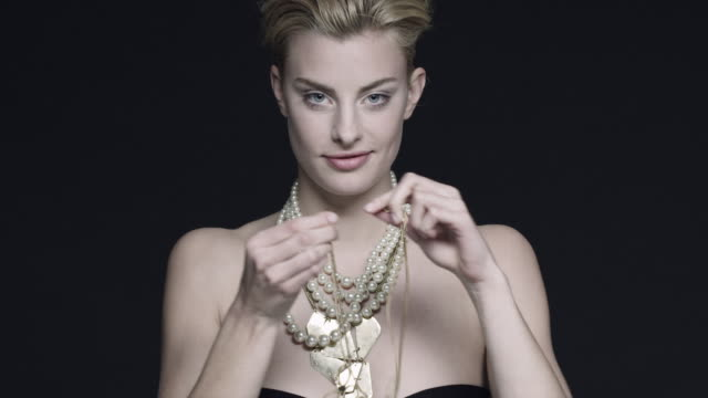 vídeos de stock, filmes e b-roll de a models places necklaces around her neck during a photo shoot in germany. - colar
