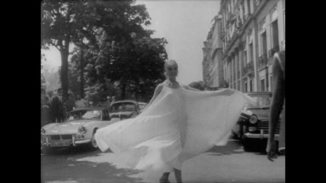 Models pose outside Jacques Heim boutique in Paris / three women in spring dresses walk down the street / single model in flared mini dress / models...