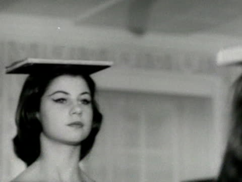 vídeos y material grabado en eventos de stock de models walk with books on their heads during a deportment class at the lucy clayton modelling school. - postura