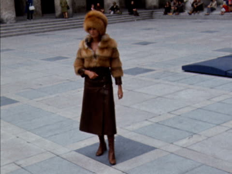 a models walks and poses wearing a fur jacket and cossack hat with a leather skirt 1970 - pelliccia materiale tessile video stock e b–roll
