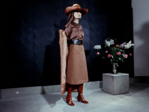 stockvideo's en b-roll-footage met a models wears a brown coat blouse and skirt with a large stetson style hat 1970 - blouse