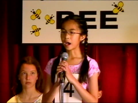 Moderator of spelling bee announcing word from behind podium / pan to girl spelling word at microphone / sitting down / Los Angeles, California