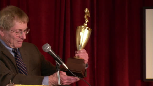 moderator of spelling bee presenting trophy to boy / boy hoisting trophy above head / zoom in to trophy / los angeles, california - trophy award stock videos & royalty-free footage