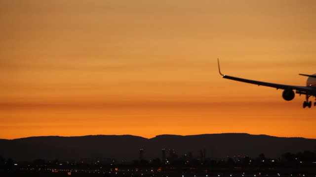 hd modern airplane landing in sunset - runway stock videos and b-roll footage