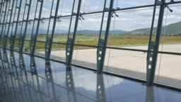 Modern airport, beautiful view of runway and passenger terminal through window. Mountains background