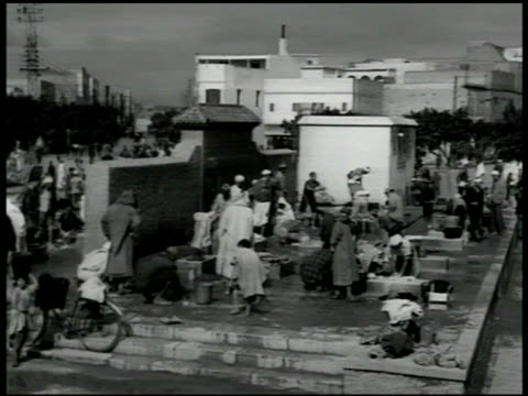 modern apartment building cattle in dirt fg slums people washing clothes in square crowd of 'water peddlers' crowding into bathhouse man adding... - 1951 stock videos and b-roll footage