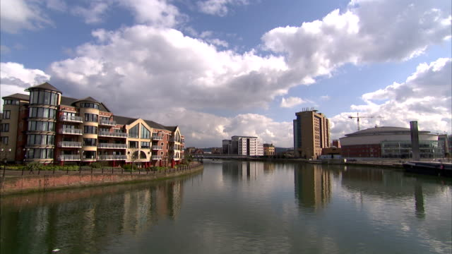 modern apartment buildings sit across the river lagan from the belfast waterfront hall. available in hd. - river lagan stock videos & royalty-free footage