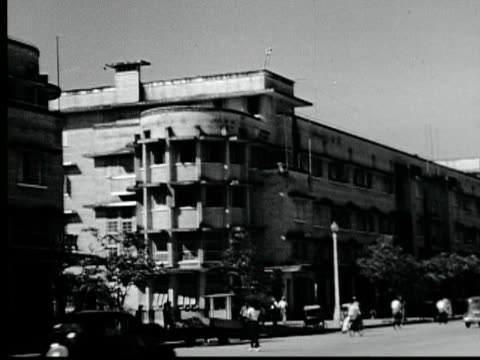 1948 b/w montage modern apartment buildings. woman carries baskets. city streets with traffic. spirit of democracy monument. motorbikes, bicycles / bango, thailand - 1948 stock-videos und b-roll-filmmaterial