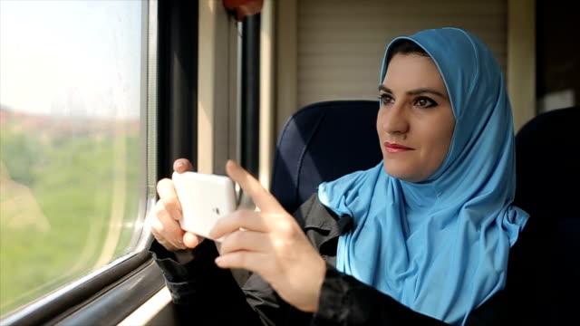 電車の中を撮影するため携帯電話を使用して、ビジネス旅行で現代のアラブ実業家 - モデスト・ファッション点の映像素材/bロール