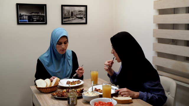modern arab family-mother and daughter have a lunch and talking at home - islam stock videos & royalty-free footage