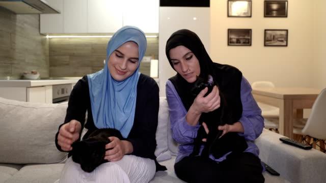 現代のアラブの家族、母と娘はペットと一緒に家でリラックス、2匹の黒猫 - 黒猫点の映像素材/bロール