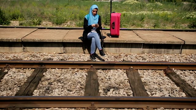 modern arab girl waiting for a train on train station and using mobile phone for fun - modest clothing stock videos & royalty-free footage