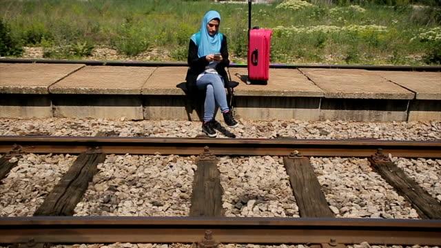 vídeos de stock, filmes e b-roll de menina árabe moderna esperando por um trem na estação de trem e usando o celular para se divertir - vestuário modesto