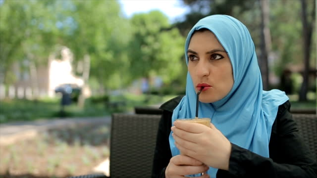 vídeos de stock, filmes e b-roll de mulher árabe moderna desfrutando no café ao ar livre - vestuário modesto