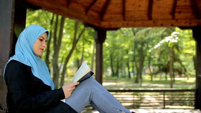 vídeos de stock, filmes e b-roll de mulher árabe moderna, lendo um livro de férias no parque - vestuário modesto