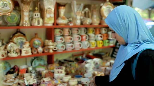 Modern Arab young woman with backpack buying souvenirs on vacation