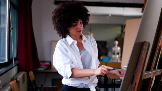 Modern artist chaotically painting on canvas