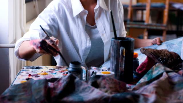 Moderne kunstenaar mengen van kleuren en schilderen op doek